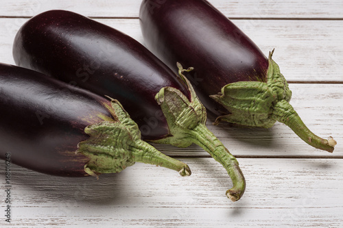 Three fresh eggplants on a white wooden surface. Poster