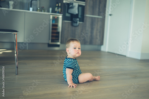 Photo  Little baby sitting on the floor in kitchen