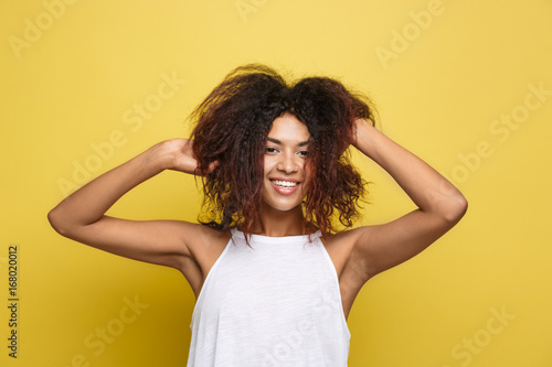 Fototapeta Beautiful attractive African American woman posting play with her curly afro hair. Yellow studio background. Copy Space. obraz na płótnie