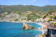 Daylight sunny day view to blue sea, beachline and green mountains. Monterosso al Mare, Italy, Cinque Terre.