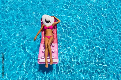 Fényképezés Attraktive Frau im Bikini treibt auf einer Luftmatratze im Pool und sonnt sich
