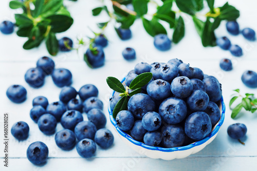 Blueberry or great bilberry in bowl on blue vintage table Wallpaper Mural
