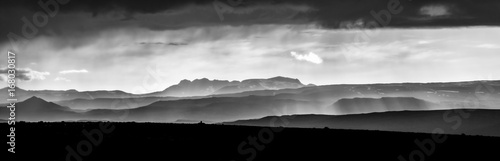 Monochrome sunset over mountains. Fantastic panorama view of misty layered icelandic landscape with dramatic clouds. Iceland.