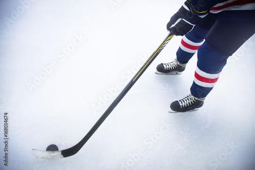 Plakat nogi hokeista na łyżwach na lodzie z kijem i krążek z bliska
