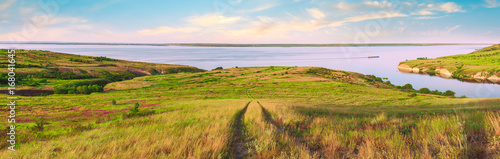 Poster Miel Scenic sea view from top of hills. Beautiful summer background. Amazing landscape with yellow meadows, green trees, blue sky, steep cliffs and picturesque bay. Panoramic photo. Camping, rest, relax.