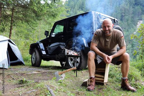 Fotografía  Mann grillt am Camping Platz vor SUV
