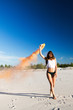 Woman walks with smoke on white beach under blue sky
