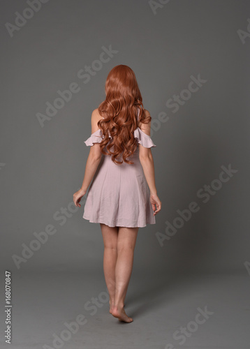 full length portrait of pr a pretty girl wearing simple purple dress, standing pose against a grey background