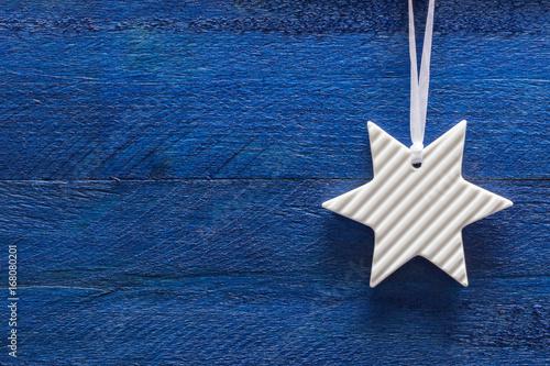Fotografía  Weihnachtskarte mit Stern auf blauem Holz