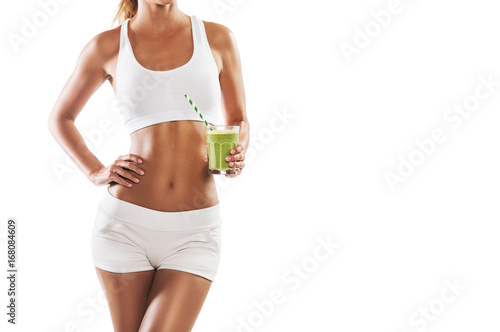 Fotografia  Fit young woman holding a healthy, green smoothie, isolated on white background,