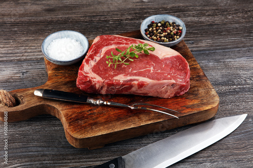 Photo  Raw fresh meat Ribeye Steak, seasoning and meat fork on dark background