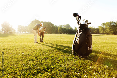 Fotografía  Senior male coach teaching young sportsman how to play golf