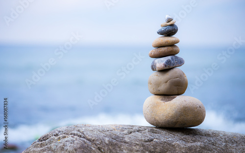 Photo  A stack of round stones standing on the shore of a sea