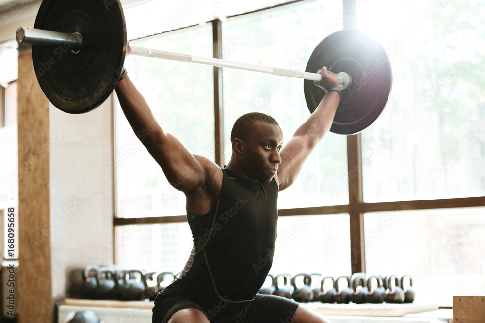 Fototapeta Strong muscular african sportsman with barbell at the gym