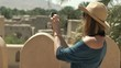 Woman taking photo with cellphone of ancient fort in Oman