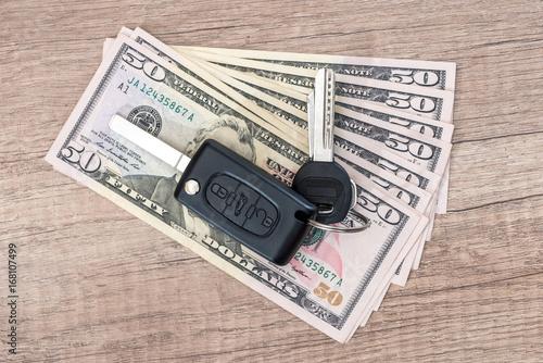 Car key lying on US 50 dollar bills on wooden desk  - Buy