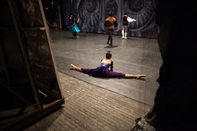 Ballet, Theater, Background. On Backstage Of Theater Dancers Are Rehearsing, Ballerina Dressed In Gorgeous Costume In Purple Shades And With Red Hair Doing The Splits Nearby Decoration