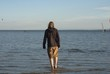 Man in a hooded sweatshirt wading in the sea