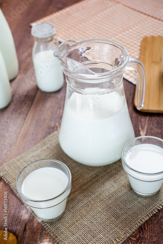 Fotobehang Zuivelproducten milk and glasses of milk on a wooden rustic table.