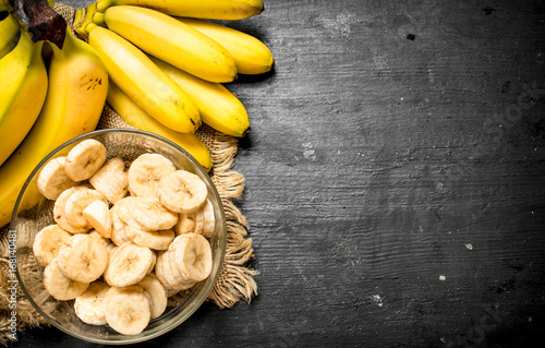 Fotografie, Obraz  Ripe bananas with pieces of sliced bananas in a bowl .