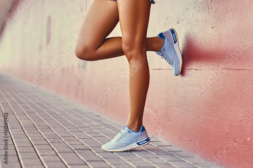 Fototapeta Close up  tans woman's legs in a white sneakers.