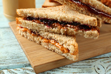 Tasty Peanut Butter And Jelly Sandwiches On Wooden Board