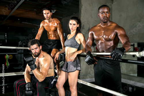 Fototapeta Diverse team of fitness exercise trainers together posing inside an MMA training