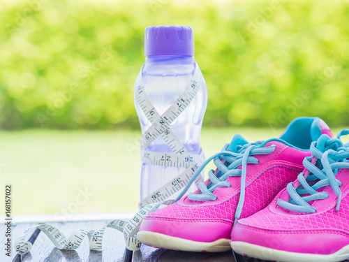 741f21898015e Pair of pink sport shoes and water bottle with green bokeh background.  Accessories for running sport.