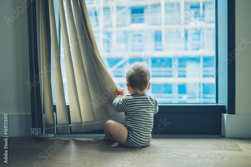 Photo  LIttle baby playing with curtain in apartment