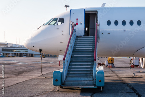 Passenger Aircraft With Boarding Stairs At The Airport Apron And Connected  To An External Power Supply
