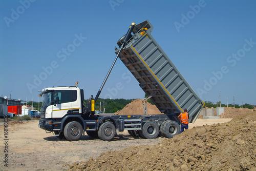 Dump Truck Unloading Soil On Construction Site