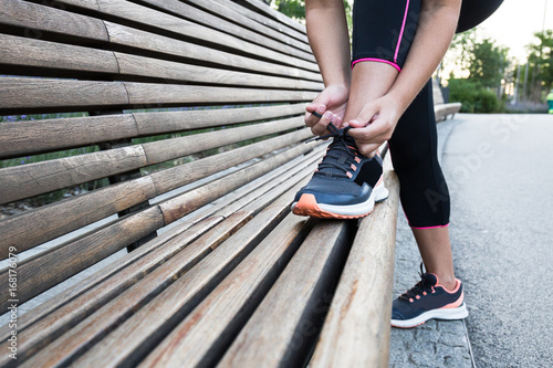 Unrecognizable fit woman tightening laces on sneakers on bench in park.