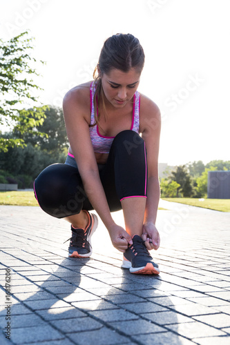 Pretty fit woman tightening sneakers during workout in the park.