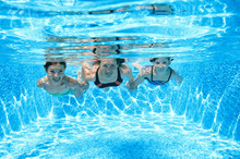Family Swims In Pool Under Water, Happy Active Mother And Children Have Fun Underwater, Fitness And Sport With Kids On Summer Vacation