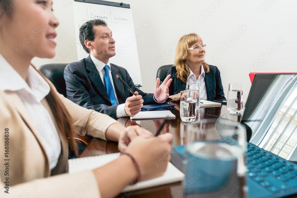 Fototapeta Geschäftsleute, Männer und Frauen, beim Meeting und der gemeinsamen Entwicklung von Ideen für besseres Business