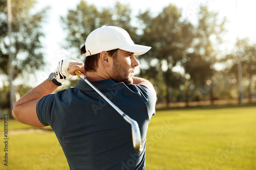 Valokuva  Close up of a young concentrated man shooting golf ball