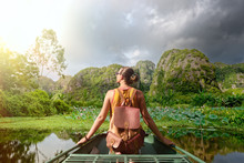 Woman Traveling By Boat On River Amidst The Scenic Karst Mountains In Ninh Binh Province, Vietnam
