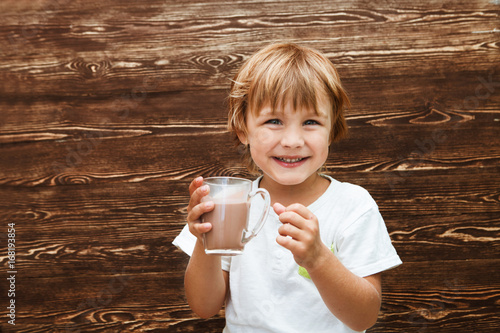 the kid drinking cocoa at home against the background of a wooden wall.