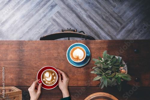 Zdjęcie XXL Widok z góry dekorowanie i projektowanie wnętrz dla kawiarni, filiżankę gorącej latte w ręku kobieta Lay na drewnianym stole