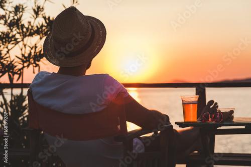 Young man enjoying sunset at a beach bar