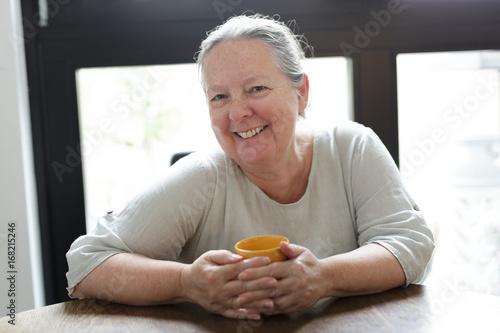 Fröhliche Seniorin sitzt mit Tasse am Tisch zuhause