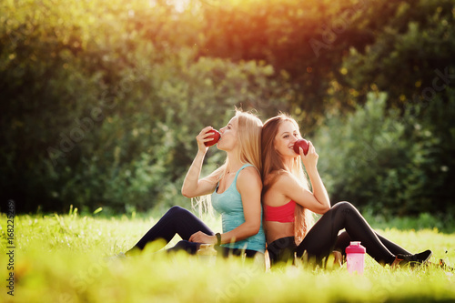 Fotografia  Group portrait of two white Caucasian girls sit together after training fitness, yoga, eating apple food