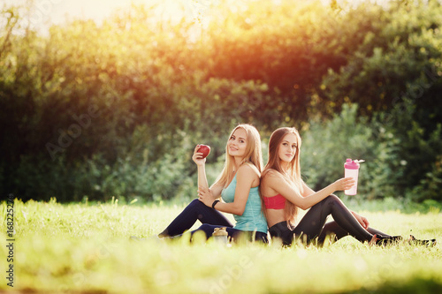 Fotografia  Group of two girls sitting on grass holding an apple and bottle of water, doing sports fitness and yoga