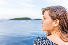 Profile Portrait Of Young Happy Smiling Woman Sitting On Edge Of Dock In Bar Harbor, Maine Looking To Side
