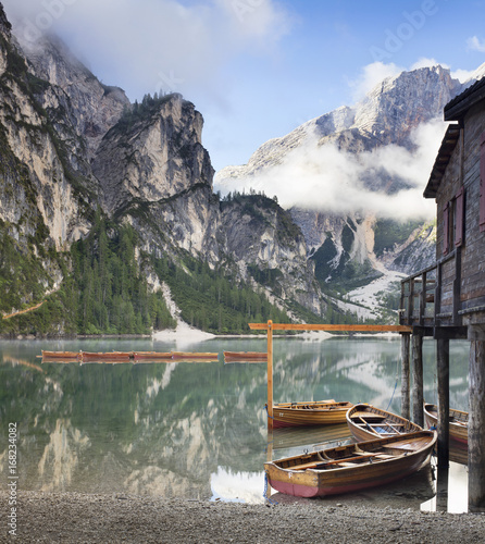 Poster Gris boats and embankment with mirror water on the lake in Italy