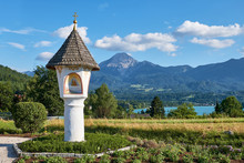 Famous Wayside Shrine In Drobollach Village In Front Of Lake Faaker And The Mountain Range Karawanken In Southern Austria