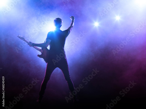 Silhouette of guitar player on stage on blue background with smoke and spotlights - 168245459