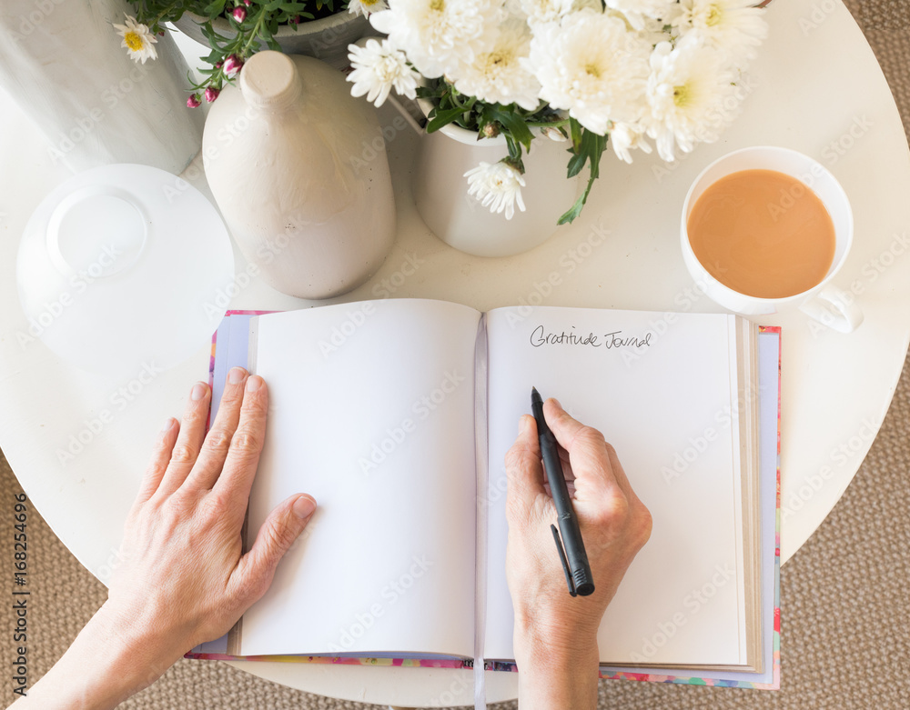 Fototapeta High angle cropped view of woman's hands writing in gratitude journal at desk with tea and flowers (selective focus)