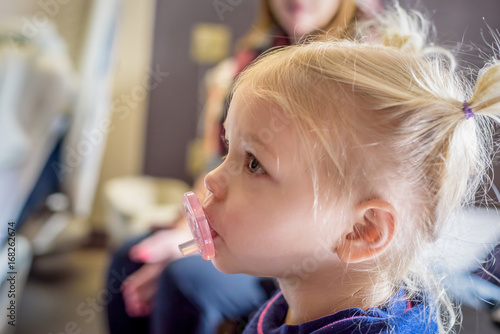 profile of little girl with pacifier and pigtails buy this stock