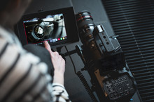 Hand Of The Camera Operator Touching A Modern DSLR